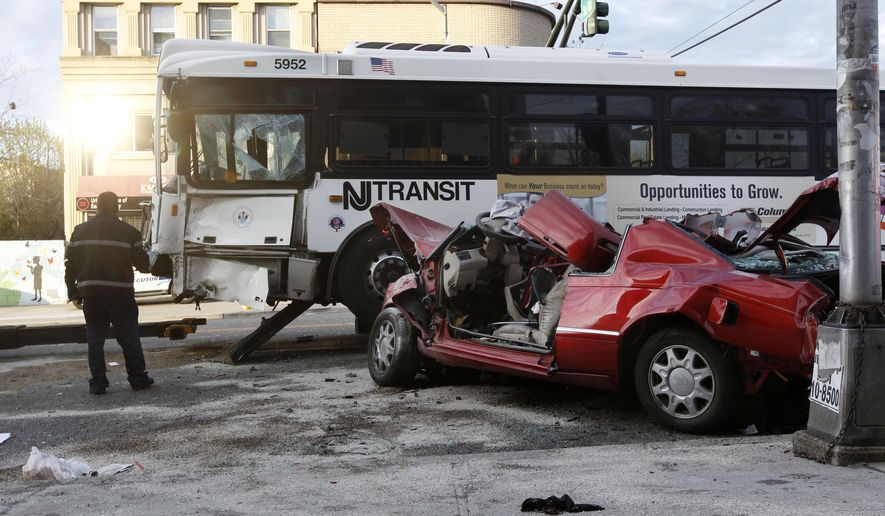 Investigators work to move a New Jersey Transit bus at the scene of a crash involving the bus and a car, Friday, May 1, 2015, in Newark, N.J. The accident happened around 2:30 a.m., and according to broadcast reports, a passenger in the car was taken to a hospital in critical condition. The bus driver and six passengers also were taken to a hospital. (AP Photo/Mel Evans)