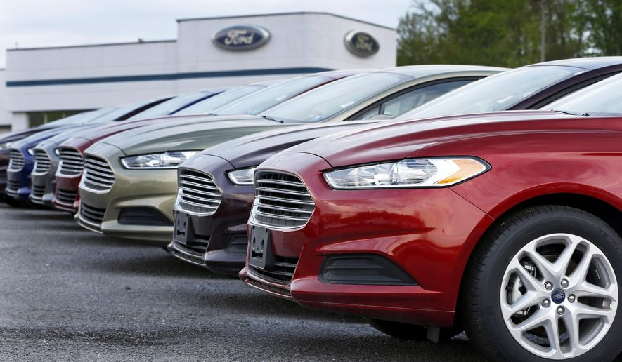 FILE - In this Wednesday, May 8, 2013 file photo, a row of new 2013 Ford Fusions are on display at an automobile dealership in Zelienople, Pa. Under pressure from U.S. safety regulators, Ford is expanding a recall of small and midsize cars to fix door latches that may not stay closed. The recall now covers almost 546,000 Ford Fusions and Lincoln MKZs from the 2013 and 2014 model years, and Ford Fiestas from 2011 to 2014. (AP Photo/Keith Srakocic, File)