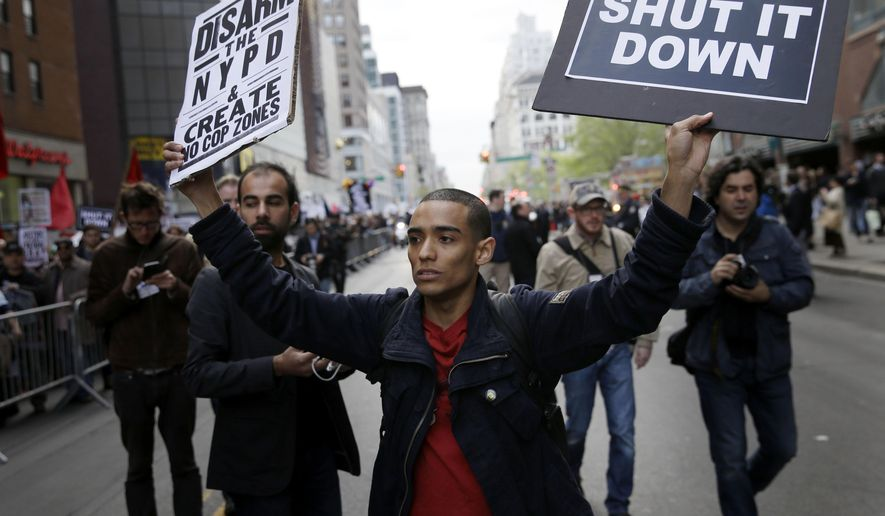 A protester walks outside of police barricades during a march in New York, Friday, May 1, 2015. About 1,000 protesters decrying police brutality marched in Manhattan at a May Day rally that took on a new message amid national outrage over a Baltimore man's death in police custody. (AP Photo/Seth Wenig)