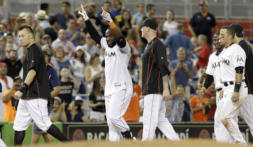 Miami Marlins' Marcell Ozuna celebrates  after hitting the game winning double against the Philadelphia Phillies in the ninth inning of a baseball game, Friday, May 1, 2015, in Miami. Giancarlo Stanton scored on the double. The marlins won 4-3. (AP Photo/Alan Diaz)