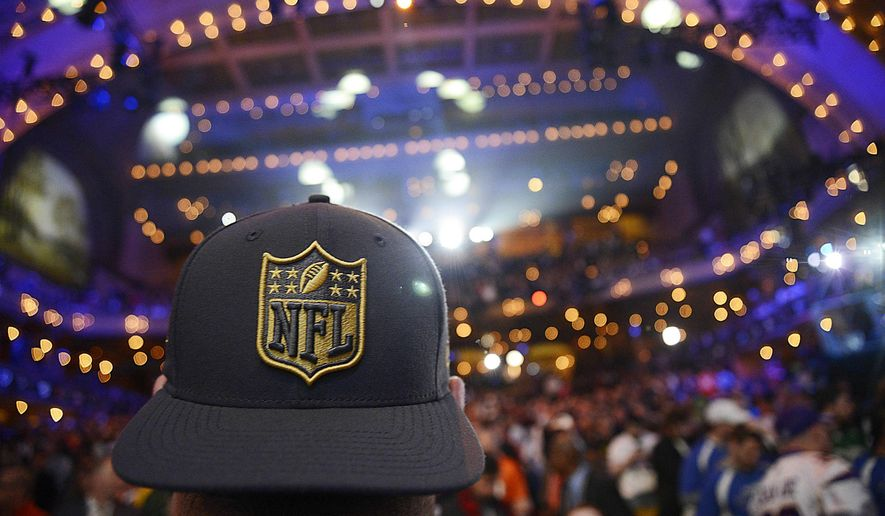 A fan turns his NFL 2015 Drift cap backward as he watches the crowd in the first round of the 2015 NFL Draft, Thursday, April 30, 2015, in Chicago. (John Starks/Daily Herald via AP)
