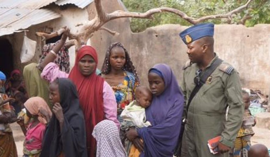 In this photo made available by the Nigerian Military taken Wednesday, April 29, 2015, a Nigerian soldier stands next to woman and children that were allegedly rescued by the Nigerian Military after being taken by Islamic extremists in Sambisa Forest, Nigeria. Scores more women and children have been rescued from Islamic extremists in the remote Sambisa Forest, Nigeria's military said amid reports that some of the women fought their rescuers fiercely. (Nigerian Military via AP)