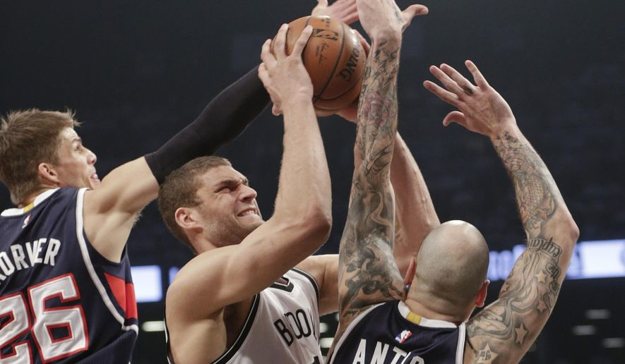 Atlanta Hawks' Kyle Korver (26) and Pero Antic (6) defend Brooklyn Nets' Brook Lopez during the first half of Game 6 in a first round NBA playoff basketball game Friday, May 1, 2015, in New York. (AP Photo/Frank Franklin II)