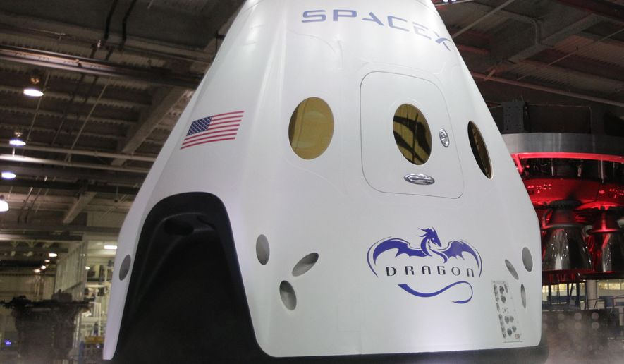FILE - In this May 29, 2014 file photo, The SpaceX Dragon V2 spaceship is unveiled at its headquarters  in Hawthorne, Calif.  SpaceX is just days away from shooting up a crew capsule to test a launch escape system designed to save astronauts' lives. Buster, the dummy, is already strapped in for Wednesday, May 6, 2015, nearly mile-high ride from Cape Canaveral, Florida. He'll be alone as the capsule is fired from a ground test stand and soars out over the Atlantic, then parachutes down. (AP Photo/Jae C. Hong)