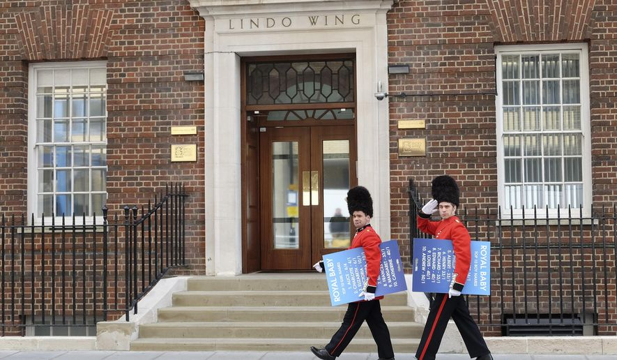 Men dressed as soldiers walk along carrying boards with proposed baby names on, outside the Lindo Wing of St Mary's Hospital in London, Friday, May 1, 2015. Kate, The Duchess of Cambridge is due to give birth at the hospital in the next few days. (AP Photo/Kirsty Wigglesworth)