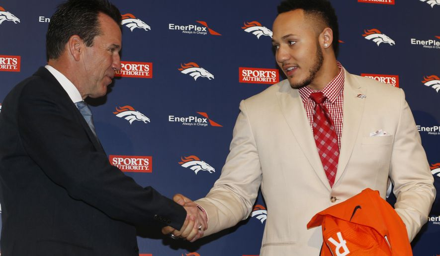 Denver Broncos head coach Gary Kubiak, left, shakes hands with Shane Ray, the team's first-round pick in the NFL Draft, before a news conference Friday, May 1, 2015, in Englewood, Colo. (AP Photo/David Zalubowski)