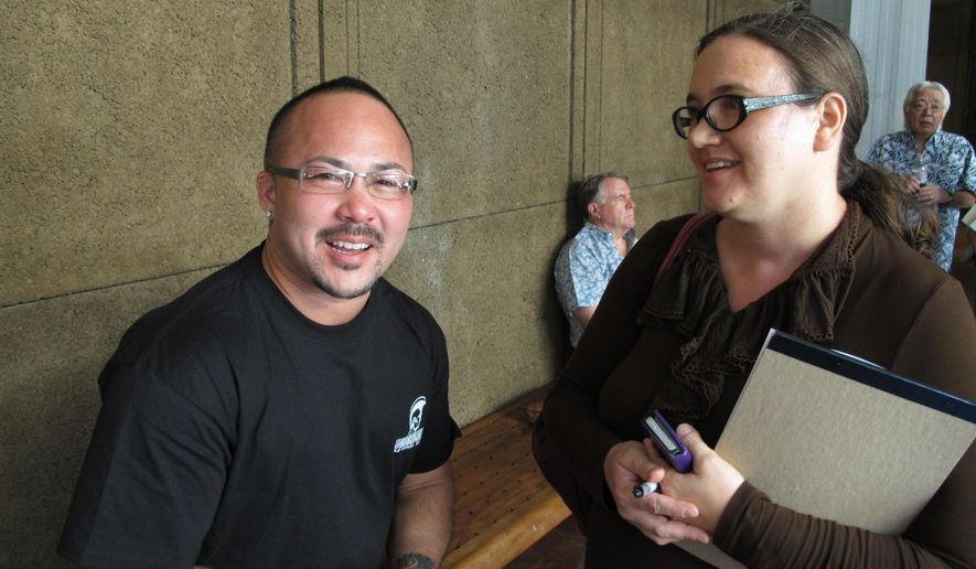 Kaleo Ramos, left, and Rebecca Copeland, right, react outside a legislative hearing room on Thursday, April 30, 2015, in Honolulu. A key committee had just passed a bill that would enable transgender people to change gender on their birth certificates without having to undergo gender reassignment surgery. (AP Photo/Cathy Bussewitz)