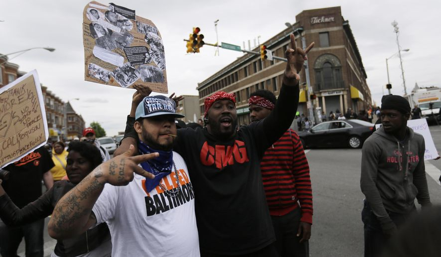 A man who calls himself Goldie Loc, left, walks with a man who calls himself Wolfe celebrating on Friday, May 1, 2015, after State's Attorney Marilyn J. Mosby announced criminal charges against all six officers suspended after Freddie Gray suffered a fatal spinal injury while in police custody in Baltimore. Loc said he is a member of the Crips gang and Wolfe said he was with the Bloods gang. (AP Photo/David Goldman)