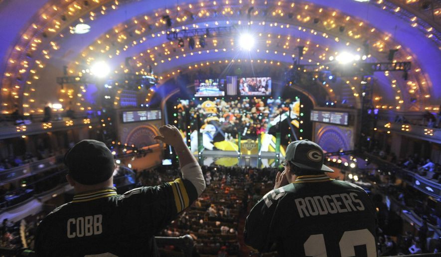 Green Bay Packers fans cheer during the first round of the 2015 NFL Football Draft,  Thursday, April 30, 2015, in Chicago. (AP Photo/Paul Beaty)
