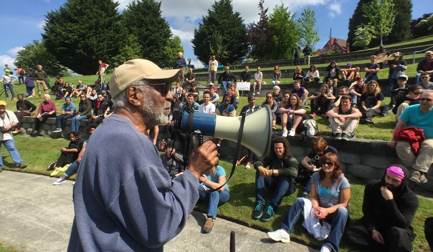 Activist Mark Cook speaking to the crowd at the Black Lives Matter rally Friday, May 1, 2015 in Seattle.  (Steve Ringman/The Seattle Times via AP) SEATTLE OUT; USA TODAY OUT; MAGS OUT; TELEVISION OUT; NO SALES; MANDATORY CREDIT TO BOTH THE SEATTLE TIMES AND THE PHOTOGRAPHER