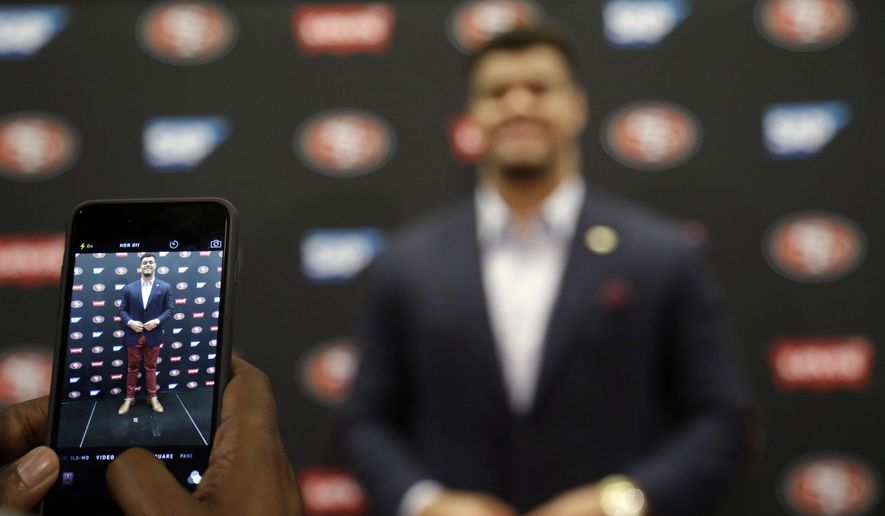 San Francisco 49ers first-round draft pick Arik Armstead, right, has his photo taken on the stage by his father Guss after an NFL football news conference Friday, May 1, 2015, in Santa Clara, Calif. (AP Photo/Marcio Jose Sanchez)