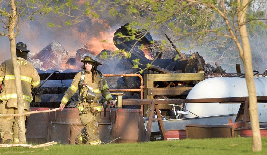 Area fire departments respond to a structural fire on 210th Street in Sergeant Bluff, Iowa, Thursday, April, 30, 2015. Authorities say flames from a northwest Iowa yard waste fire spread to a barn after the man tending the fire went inside for dinner. Firefighters were sent to the Sergeant Bluff property a little before 7 p.m. Thursday. Crews from eight departments kept the blaze from igniting gasoline and other fuels inside the barn and spreading to a large propane tank nearby. Benson says the man tending the fire didn't need a permit to burn the yard waste and won't be cited.  (Justin Wan/The Sioux City Journal via AP)