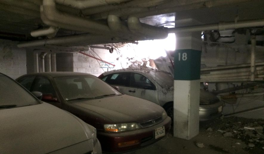 Parked cars are seen near a part of collapsed structure at the Watergate complex in Washington, Friday, May 1, 2015. District of Columbia rescuers were responding to a structural collapse in the garage at the Watergate complex where one person may be trapped. A spokesman said three stories of the garage apparently collapsed. The area was under construction at the time. (Minh Tran via AP)