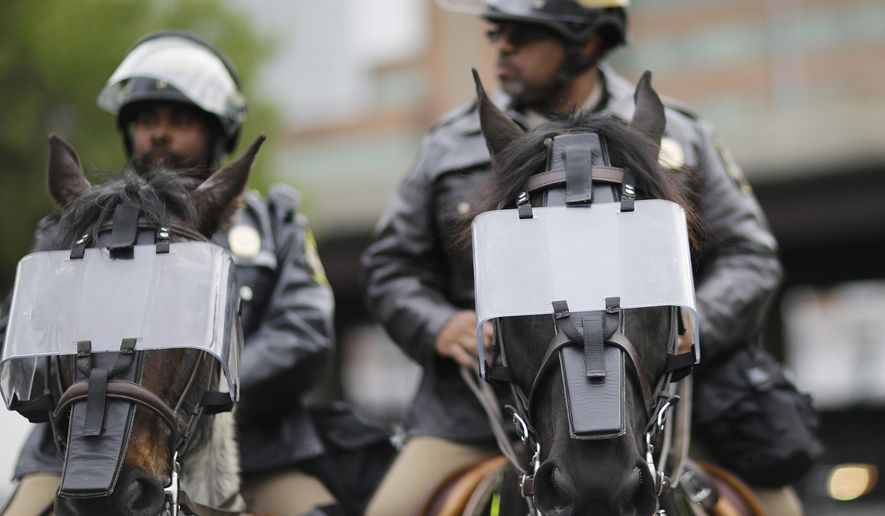Police horses wear riot shields as demonstrators march by on the way to Baltimore City Detention Center the day of the announcement of charges against the police officers involved in Freddie Gray's arrest, Friday, May 1, 2015, in Baltimore. (AP Photo/David Goldman) ** FILE **
