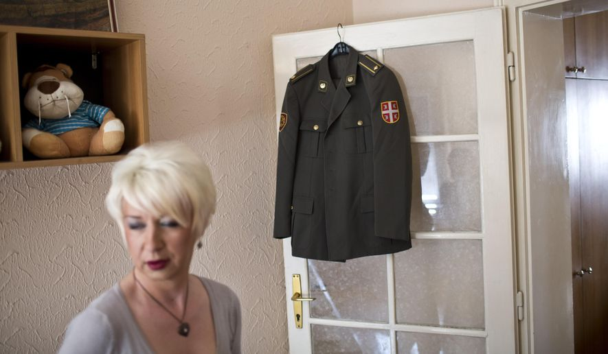 Helena, a transgender person, stands next to her Serbian army uniform put on display in her friend's apartment Wednesday, April 15, 2015, in Belgrade, Serbia. (AP Photo/Marko Drobnjakovic)