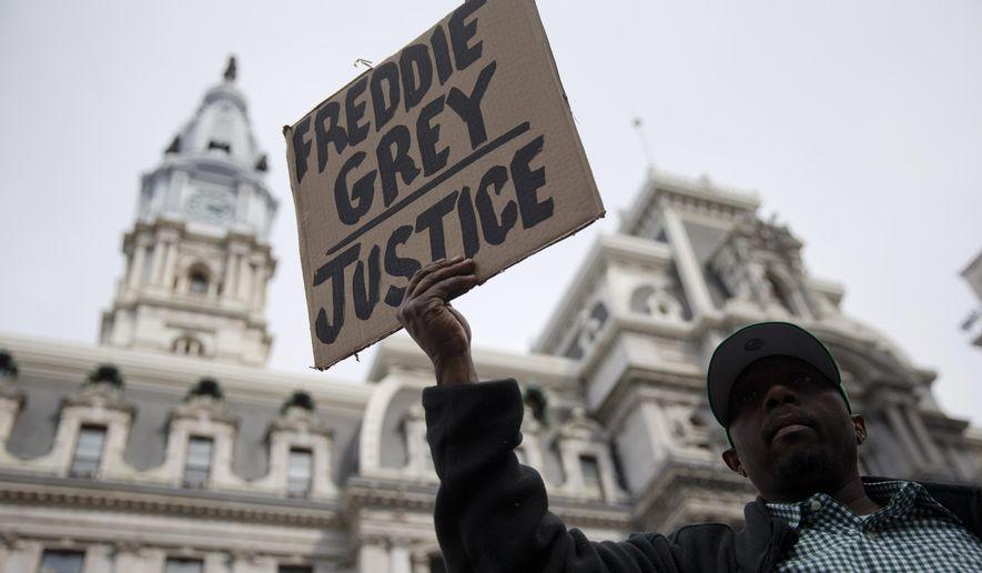 Daniel H Smith demonstrates outside City Hall in Philadelphia on Thursday, April 30, 2015. The event in Philadelphia follows days of unrest in Baltimore amid Freddie Gray's police-custody death. (AP Photo/Matt Rourke)