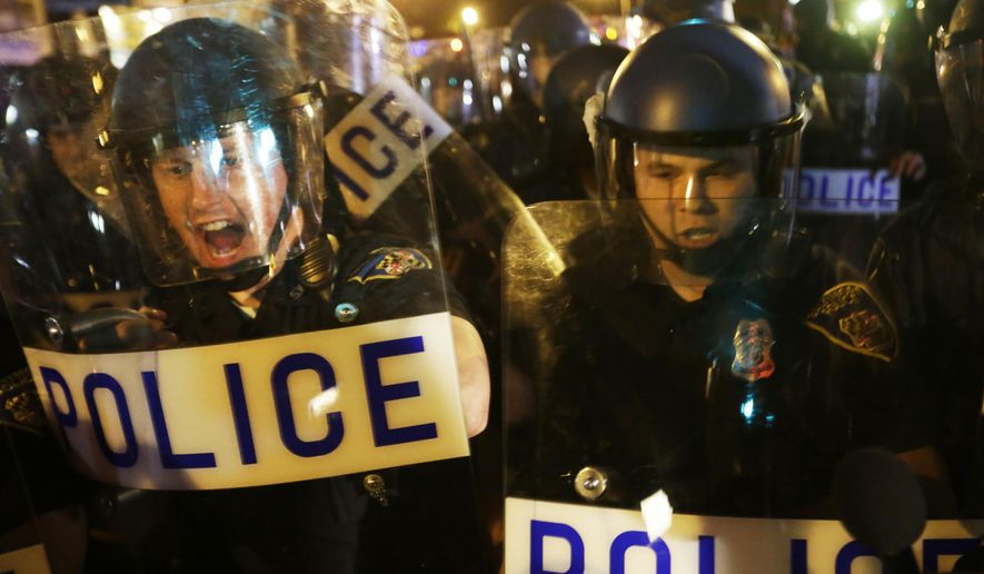 Police in riot gear push back on media and a crowd gathering in the street after a 10 p.m. curfew went into effect Thursday, April 30, 2015, in Baltimore. The curfew was imposed after unrest in the city over the death of Freddie Gray while in police custody. (AP Photo/David Goldman)
