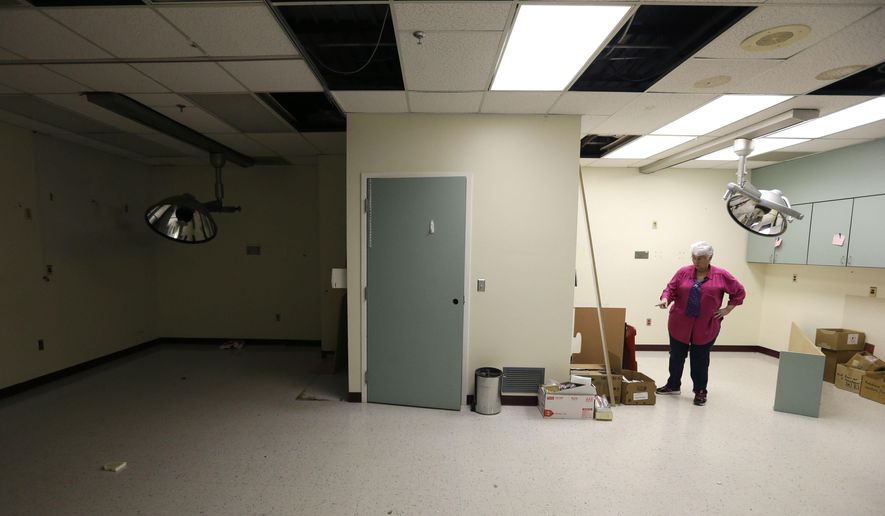 In this April 1, 2015, photo, Chris Smiley, the hospital's last chief executive, stands in the empty emergency room of Sac-Osage Hospital in Osceola, Mo.. After 45 years of providing health care in rural western Missouri, Sac-Osage Hospital is being sold piece by piece. (AP Photo/Orlin Wagner)