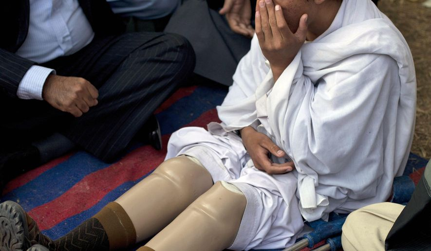 FILE - In this Dec. 10, 2010, file photo, Pakistani tribal youth Saadullah Wazir, who reportedly lost his legs in a drone attack, sits during a protest in Islamabad, Pakistan. People in Pakistan who live under the threat of U.S. drone strikes see a double standard at work in Washington. In April 2015, President Barack Obama took the unusual step of acknowledging and apologizing for a highly secret U.S. drone strike that accidentally killed an American and an Italian aid worker held captive by al-Qaida in Pakistan. (AP Photo/B.K. Bangash, File)