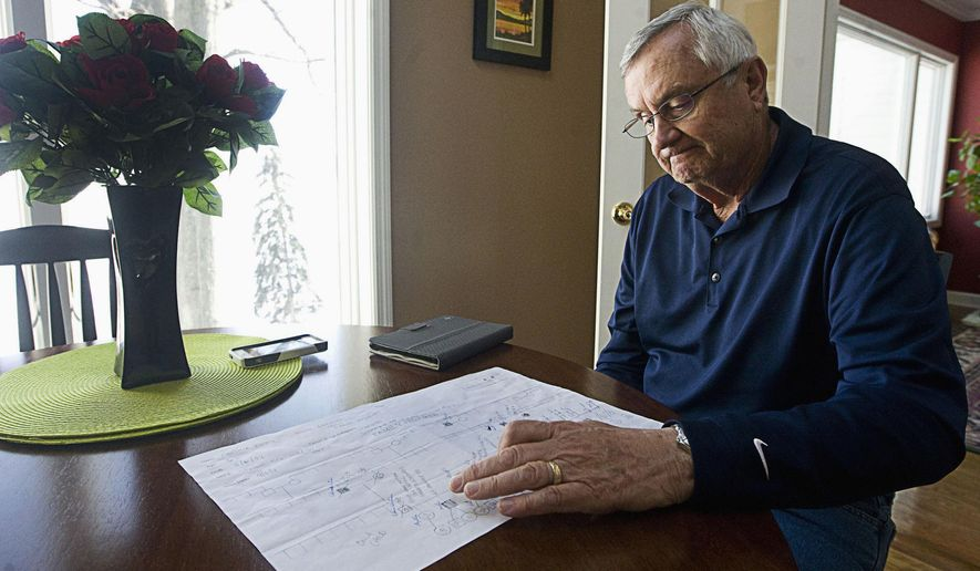 In this March 6, 2015 photo, Mike Wortman looks over a chart of his family and those who have tested positive for Lynch Syndrome at his home in Decatur, Ill. Wortman has discovered his family is predisposed to the genetic cancer. (Lisa Morrison/Herald & Review via AP)