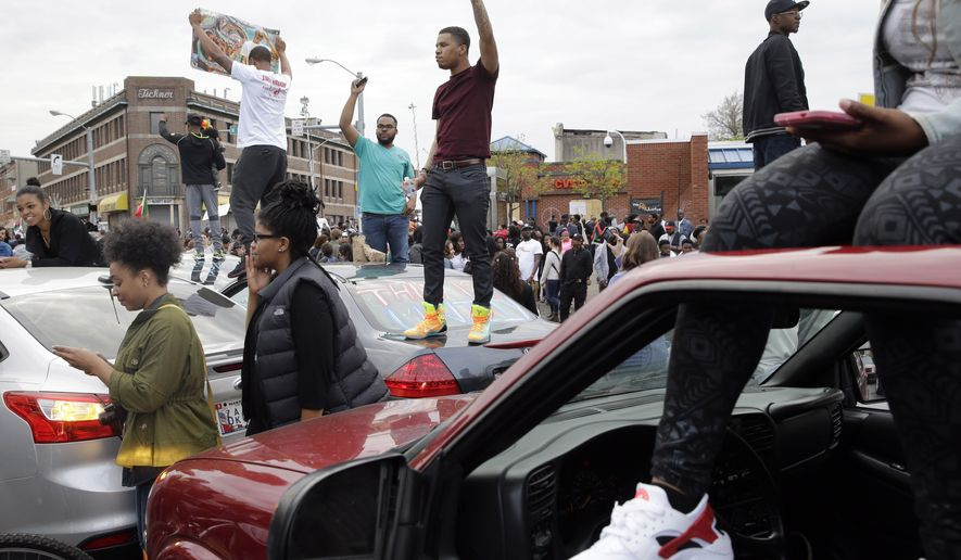 """Protesters stand on cars near the intersection of North Avenue and Pennsylvania Avenue in Baltimore, Friday, May 1, 2015, the day of the announcement of charges against the police officers involved in Freddie Gray's arrest. State's Attorney Marilyn Mosby announced the stiffest charge, second-degree """"depraved heart"""" murder, against the driver of the police van that Gray was in after his arrest. Other officers faced charges of involuntary manslaughter, assault and illegal arrest. (AP Photo/Patrick Semansky)"""