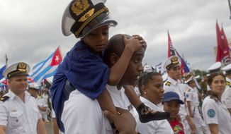 A Cuban navy soldier carries a child on his shoulders as they march in Revolution Square marking May Day, in Havana, Cuba, Friday, May 1, 2015. Thousands of people converged on the plaza for the traditional march, led this year by President Raul Castro and Venezuelan President Nicolas Maduro. (AP Photo/Ramon Espinosa)