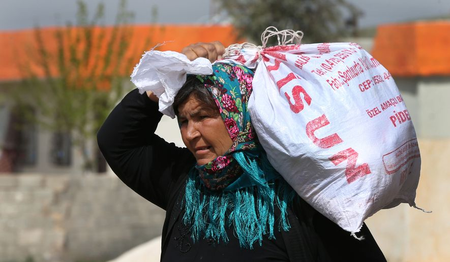In this picture taken on Monday, April 20, 2015, a Kurdish refugee woman who fled from Kobani carries her belongings as she walks toward a border gate to return to her town, at the Mursitpinar border crossing in Suruc town, Turkey. Three months since Kobani was liberated, tens of thousands of its residents are still stranded in Turkey, reluctant to return to a wasteland of collapsed buildings and at a loss as to how and where to rebuild their lives. (AP Photo/Hussein Malla)
