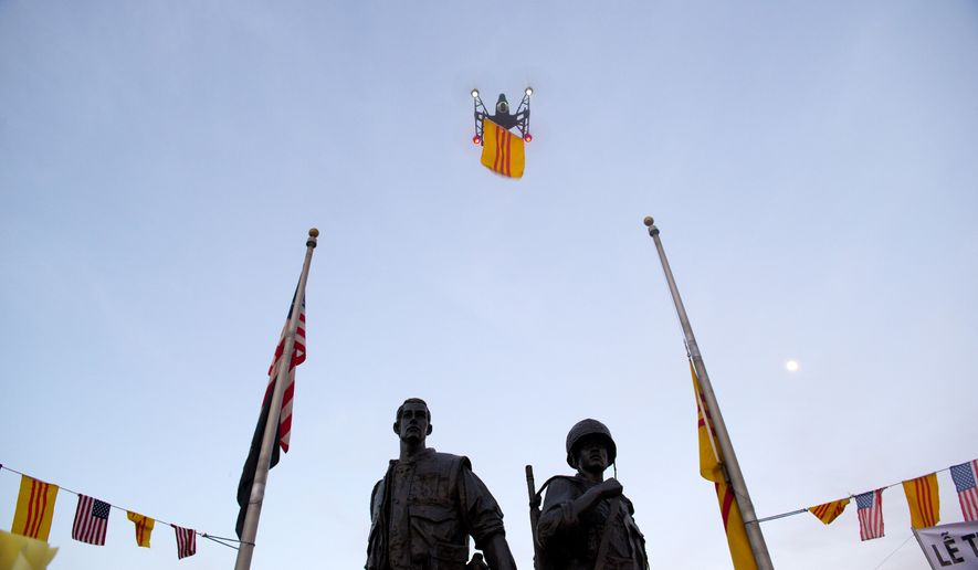 A drone carrying the flag of South Vietnam flies above during a commemoration for the 40th anniversary of the fall of Saigon, at Sid Goldstein Freedom Park in Westminster, Calif., on Thursday, April 30, 2015. (Matt Masin/The Orange County Register via AP)   MAGS OUT; LOS ANGELES TIMES OUT; MANDATORY CREDIT
