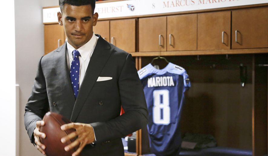 Marcus Mariota, former Oregon quarterback and overall No. 2 NFL football draft pick by the Tennessee Titans, poses for photos in the locker room Friday, May 1, 2015, in Nashville, Tenn. Mariota was selected by the Titans in the first round Thursday. (AP Photo/Mark Humphrey)