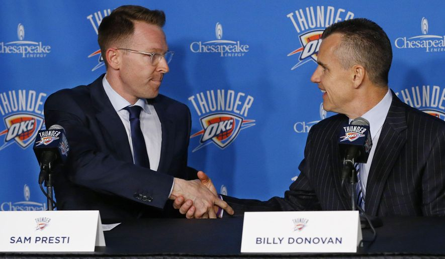 Billy Donovan, right, the new head coach of the Oklahoma City Thunder, shakes hands with general manager Sam Presti, left, during an NBA basketball news conference Friday, May 1, 2015, in Oklahoma City. (AP Photo/Sue Ogrocki)