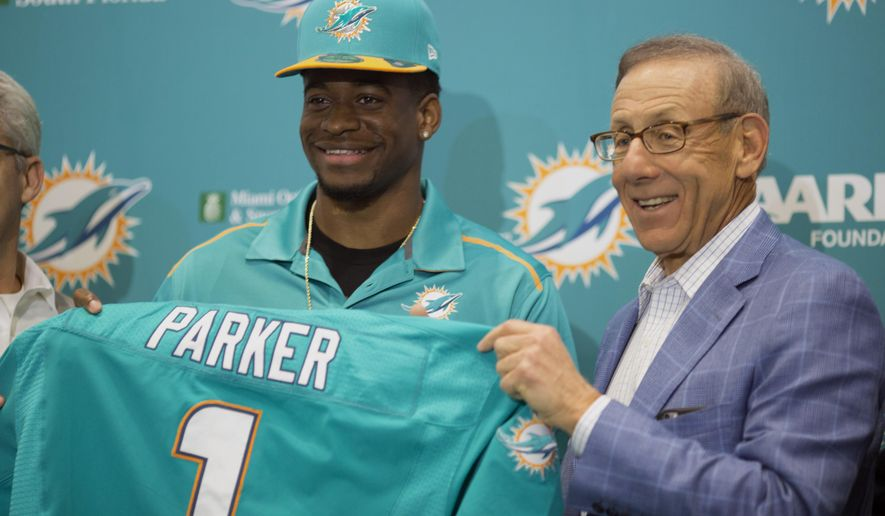DeVante Parker, the Miami Dolphins' first round draft choice, and team owner Stephen Ross display a team jersey, as they talk to the media, during a news conference at the Dolphins headquarters in Davie, Fla., Friday, May 1, 2015.  (AP Photo/J Pat Carter)