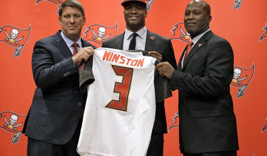 Tampa Bay Buccaneers first-round draft pick Jameis Winston, center, holds his jersey as he stands with general manager Jason Licht, left, and head coach Lovie Smith, right, during a news conference Friday, May 1, 2015, in Tampa, Fla. Winston, a former Florida State quarterback, was the first overall pick. (AP Photo/Chris O'Meara)