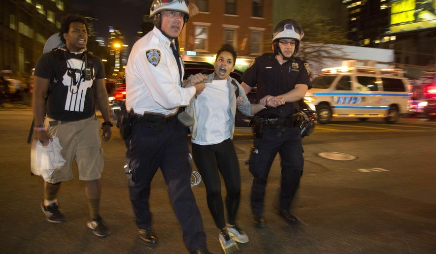 New York City police escort a woman off the street and back onto the sidewalk where she was released during a protest, Wednesday, April 29, 2015, in New York. Several hundred people gathered in New York on Wednesday to protest the death of Freddie Gray, a Baltimore man who was critically injured in police custody, and more than a dozen were arrested. (AP Photo/Julie Jacobson)