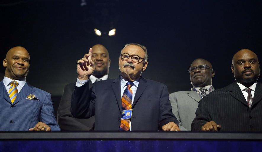 NFL Hall of Famer Dick Butkus acknowledges fans as he stands with former NFL players during the second round of the 2015 NFL Football Draft,  Friday, May 1, 2015, in Chicago. (AP Photo/Charles Rex Arbogast)