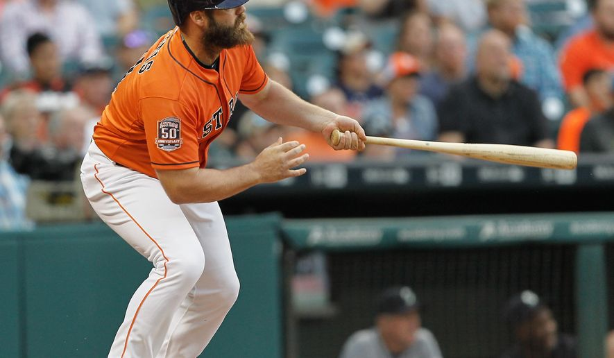 Houston Astros designated hitter Evan Gattis (11) hits a home run in the first inning of a baseball game against the Seattle Mariners, Friday, May 1, 2015 in Houston. (AP Photo/Bob Levey)
