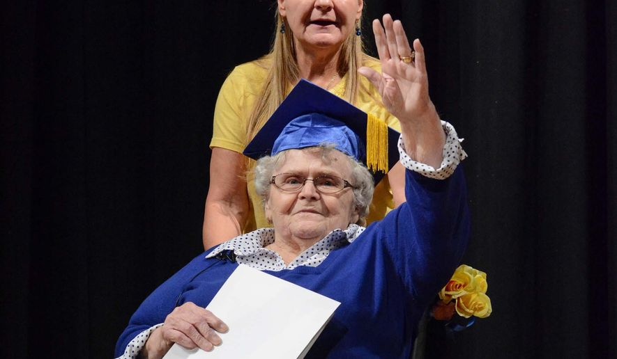In this photo taken Thursday, April 30, 2015, Susan Bostik Reynolds waves to Clearview High School students during graduation ceremonies in Lorain, Ohio. Reynolds, who missed graduation in 1952 because she needed a half-credit of gym class, received her high school diploma decades later at the surprise ceremony. Her daughter Cindy Bracy stands behind her. (Eric Bonzar/Morning Journal via AP)  (REV-SHARE)