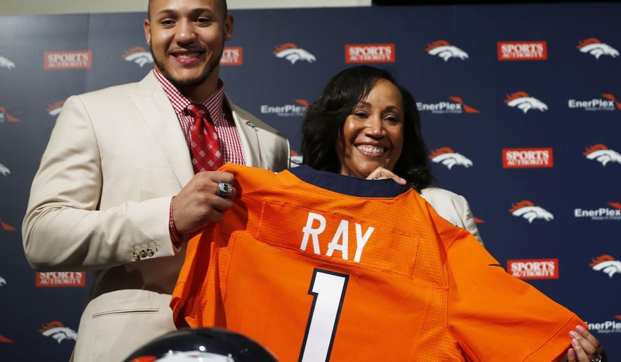 Shane Ray, left, the Missouri pass rusher selected by Denver Broncos in the first round of the NFL Draft, holds his team jersey with his mother Sebrina Johnson after a news conference Friday, May 1, 2015, in Englewood, Colo. (AP Photo/David Zalubowski)