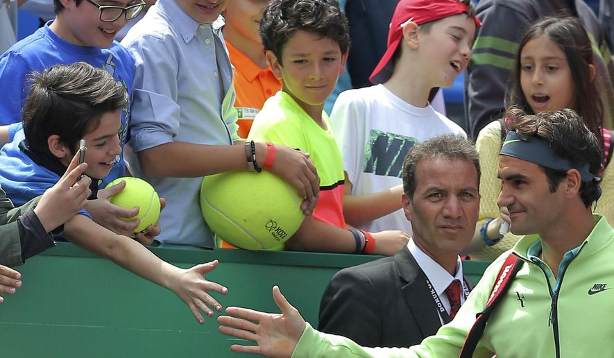 Roger Federer of Switzerland is greeted by young fans as he arrives to play a quarter final tennis match against Daniel Gimeno-Traver of Spain during the Istanbul Open tennis tournament at Garanti Koza Arena in Istanbul, Turkey, Friday, May 1, 2015. The first ever ATP World Tour event in Turkey is being played on clay from April 27, to May 3, 2015. (AP Photo)