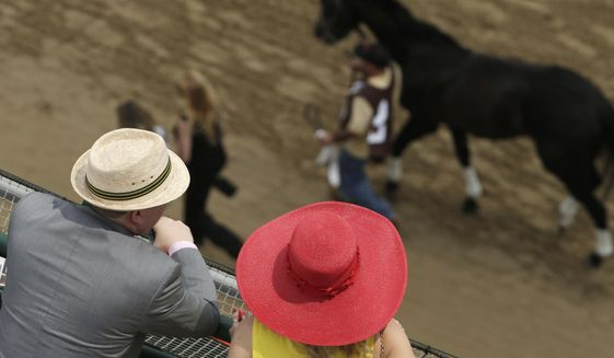 Fans watch a race before the 141st running of the Kentucky Derby horse race at Churchill Downs Saturday, May 2, 2015, in Louisville, Ky. (AP Photo/Charlie Riedel) ** FILE **