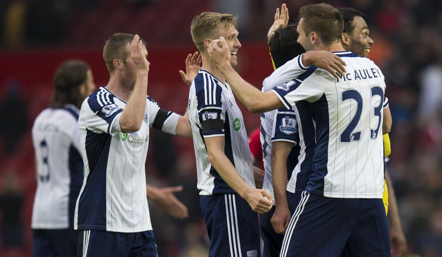 West Bromwich Albion players including captain Darren Fletcher, center, celebrate after their 1-0 win during the English Premier League soccer match between Manchester United and West Bromwich Albion at Old Trafford Stadium, Manchester, England, Saturday, May 2, 2015. (AP Photo/Jon Super)