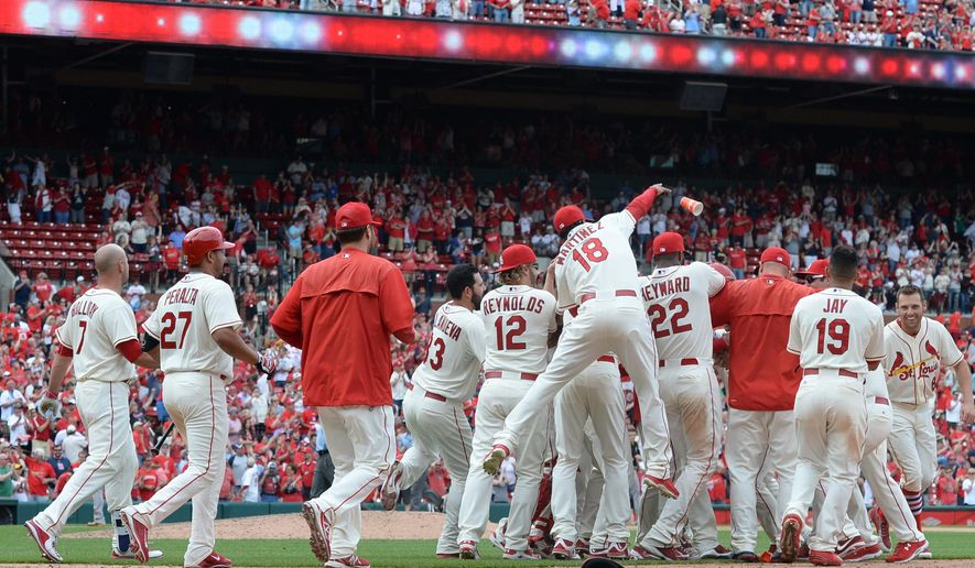 St. Louis Cardinals celebrate after a walkoff sacrifice fly by Matt Carpenter to defeat the Pittsburgh Pirates 2-1 in the eleventh inning of a baseball game, Saturday, May 2, 2015, at Busch Stadium in St. Louis. (AP Photo/Bill Boyce)