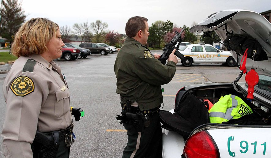 ADVANCE FOR USE SATURDAY, MAY 2 - In this photo taken Friday, April 24, 2015, Scott County, Iowa Sheriff reservists Janet Dolan, left, watches partner Troy Sullivan check a weapon before leaving Patrol Headquarters to head out into the county. (John Schultz/The Quad City Times via AP)