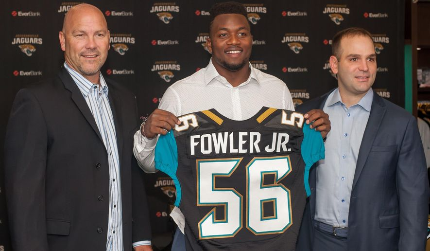 Dante Fowler, the Jacksonville Jaguars first round draft pick, holds up his jersey as he stands between head coach Gus Bradley, left, and general manager David Caldwell during an NFL football press conference at EverBank Field in Jacksonville, Fla., Saturday May 2, 2015. (Fran Ruchalski/The Florida Times-Union via AP)