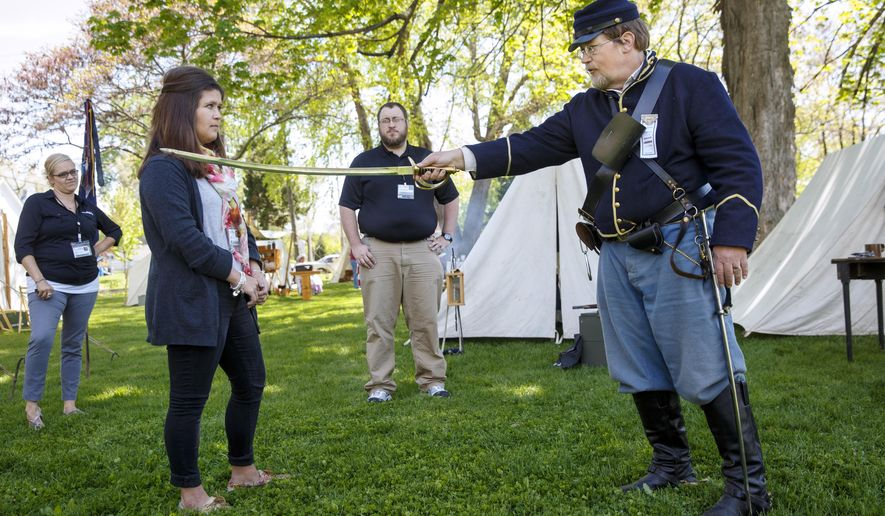Randy Weaver of Canton, Ill., a member of the 10th Illinois Volunteer Cavalry Regiment Reactivated, demonstrates how to weild a Model 1860 Light Cavalry Sabre in combat on volunteer Colleen Corcoran on the grounds of the Springfield Art Association Friday, May 1, 2015. Members of the regiment began camping on the grounds Thursday night in preparation for the 150th anniversary of Abraham Lincoln's funeral weekend.  (Ted Schurter/The State Journal-Register via AP)