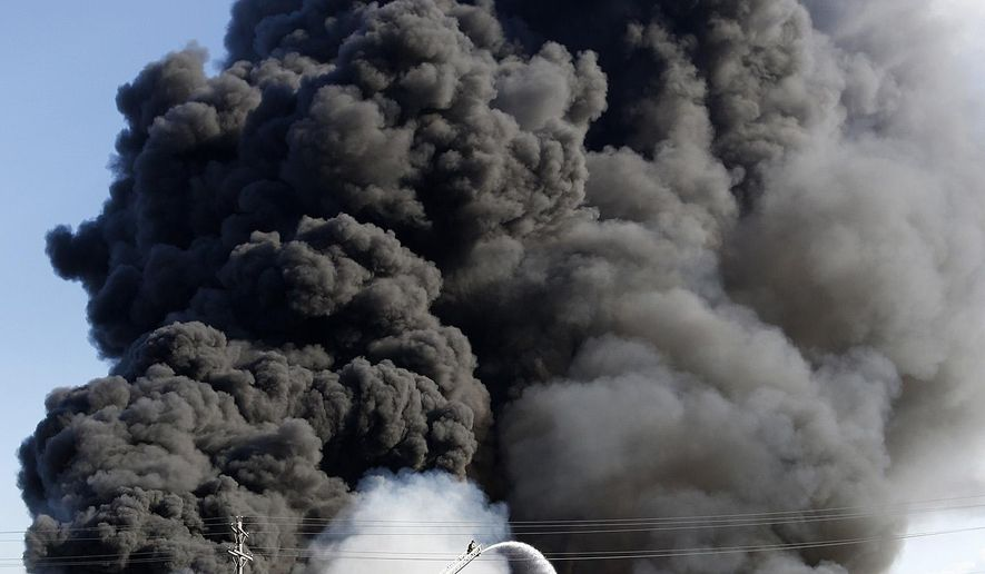 Smoke rises from a fire at a recycling facility in south Columbus, Ohio on Friday, May 1, 2015. Officials said one-third to one-half of the city's firefighters were battling the fire, and thousands of nearby residents were without power. (Eamon Queeney/Columbus Dispatch via AP)