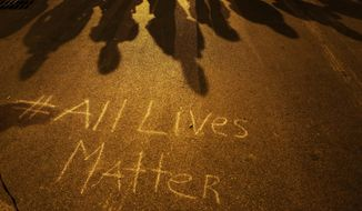 "A message reading ""All Lives Matter"" is written on the pavement as police in riot gear cast shadows while standing in line ahead of a curfew Friday, May 1, 2015, in Baltimore. (AP Photo/David Goldman) ** FILE **"