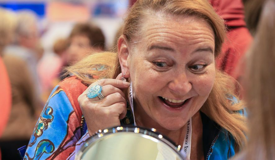 Berkshire Hathaway shareholder Tracey Halvorson, of Omaha, tries on an earring at the Borsheims booth at the CenturyLink Center exhibit hall in Omaha, Neb., Friday, May 1, 2015. Thousands of  shareholders attending this weekend's annual meeting can pick up commemorative underwear, jewelry, running shoes and other souvenirs. More than 40,000 people are expected to attend Saturday's meeting to listen to Warren Buffett and Charlie Munger. (AP Photo/Nati Harnik)
