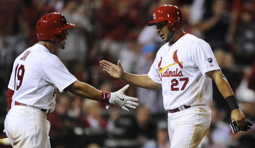 St. Louis Cardinals' Jhonny Perlata (27) is congratulated by Jon Jay (19) after scoring on a single by Mark Reynolds against the Pittsburgh Pirates in the seventh inning in a baseball game, Friday, May 1, 2015, at Busch Stadium in St. Louis. (AP Photo/Bill Boyce)