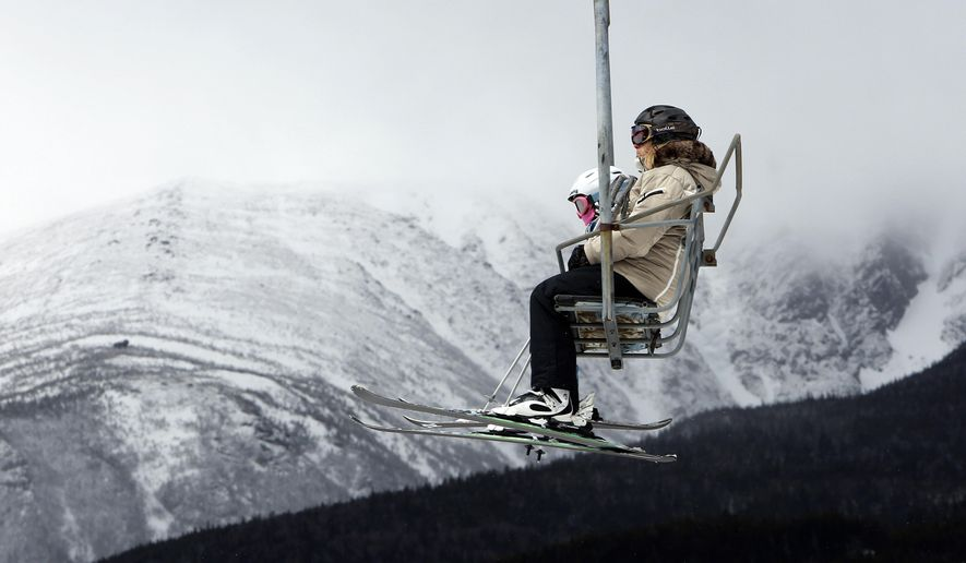 In this photo taken Saturday April 25, 2015 skiers ride the chairlift with part of Mount Washington seen in the background at Wildcat ski area in Gorham, N.H.  Resorts in many northern New England ski areas are extending their season thanks to the abundance of snow.  (AP Photo/Jim Cole)