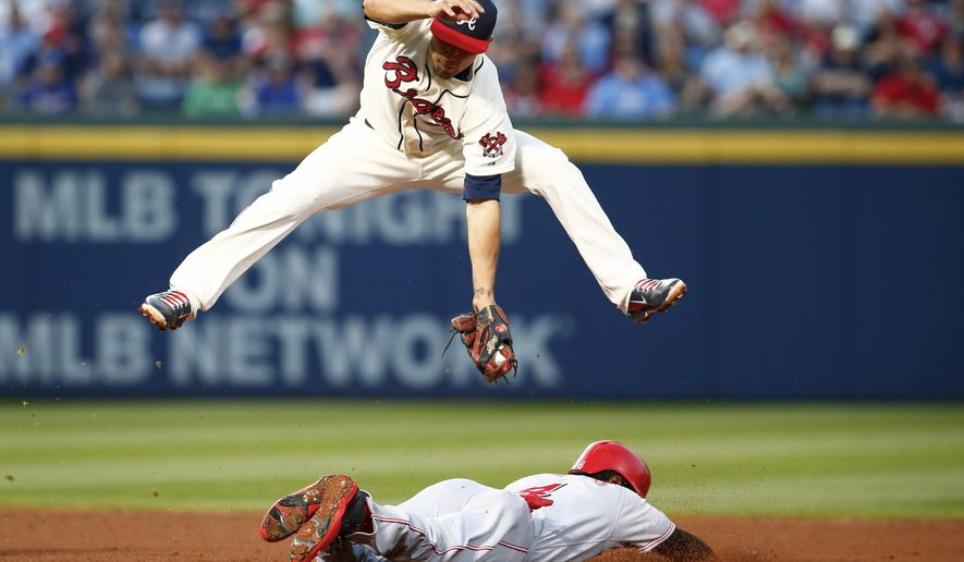 Cincinnati Reds' Brandon Phillips slides safely under Atlanta Braves second baseman Jace Peterson at second during the fourth inning of a baseball game Saturday, May 2, 2015 in Atlanta. (AP Photo/Kevin Liles)